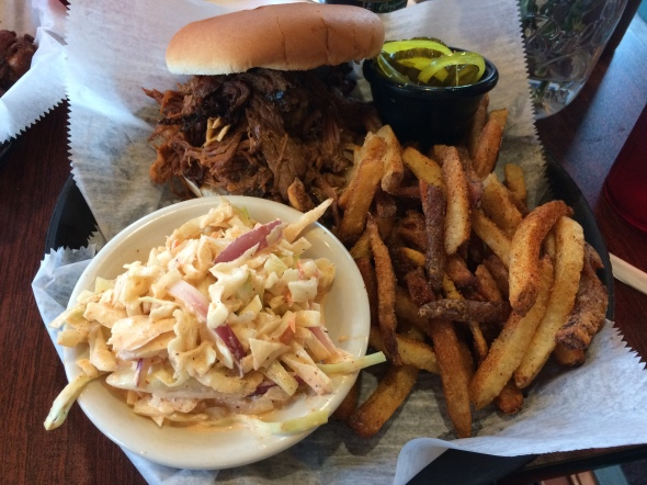 A pulled pork sandwich, coleslaw and french fries from Momma's Mustard, Pickles & BBQ.